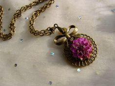 Dieser Anhänger mit Blüte in pink kombiniert mit der goldigen Bronze bringt den Frühling zu dir.  Der Anhänger kommt mitsamt der passenden Gliederkett