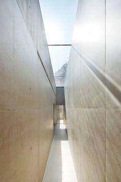 Narrow hallway + architectural concrete walls + skylight. by Found Associates.