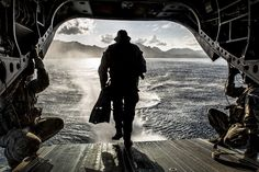 A US Army Soldier with Operational Detachment Alpha 1215, 1st Special Forces Group, Joint Base Lewis-McChord, runs off the back of a CH-47F Chinook helicopter while conducting a simulated combat dive mission in the water off of Marine Corps Training Area Bellows. The helicopter hovered the ocean and allowed the soldiers to conduct a boat movement leading to reconnaissance of the beach and a raid in the training facility at Bellows.