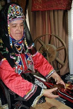 A village woman from the Keles district (south of Bursa), wearing her traditional festive costume, is making a 'çarpana kemer' (tablet/card-woven belt).