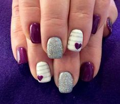 Purple, sparkles, white, and hearts nails.