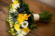 Spring wedding bouquet of daffodils, thistle and freesia
