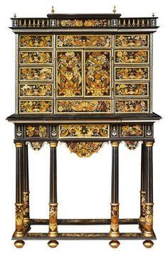 CABINET à MARQUETERIE DE FLEURS Cabinet en marqueterie de bois teinté à décor floral. Il ouvre en façade par une série de tiroirs et faux tiroirs, et par deux portes qui découvrent un théâtre à fond de glace. Il est surmonté d'une galerie de miroirs et de demi-balustres avec un léger ressaut central. Le piètement à colonnes est relié par une entretoise, et en ceinture par des arcatures décorées reprenant le même décor. époque Louis XIV H: 174,5 L: 113,1 P: 45,3 cm