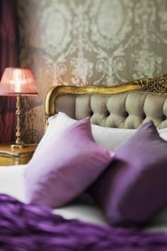 Gorgeous bedroom details. Upholstered bed with gold frame, pillows in shades of purple, and beautiful grey and cream wallpaper.