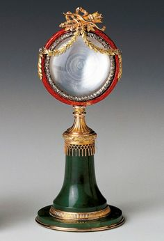 Fabergé column surmounted by a circular frame, c. 1900. Nephrite, two-colour gold, red guilloché enamel, rose diamonds, mother-of-pearl. Given to Queen Mary on her birthday by Queen Elizabeth The Queen Mother, May 26 1946.