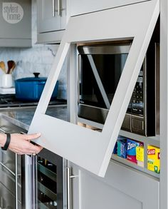 """Flip-up cabinet—Instead of using a typical trim kit, Ingrid intergrated the microwave into the kitchen cabinetry for a more seamless look. """"It's a flip-up, so if you have to access for service the microwave, you can,"""" she says."""