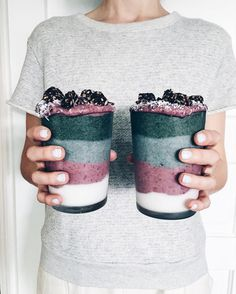 layered smoothie bottom layer: coconut milk, coconuts water, coconut shreds, and frozen bananas, next layer: blueberry banana / blue gray layer: blackberries, peaches, bananas, apples dark blue layer: black berries, blueberries with black berries and shredded coconut on top