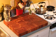 Cover an ugly counter with a cute and big cutting board {apartment Therapy}
