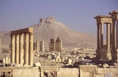 photo of Syria, Syrian desert, ruins of the Roman city of Palmyra (ancient Tadmor), the Great Colonnade and Tetrapylon with the Qala'at ibn Maan (Qalaat) fort on a hill in the background