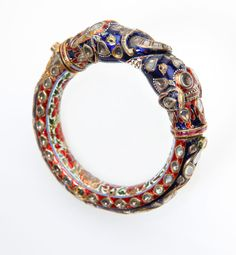 Lot# 1028 An Indian enamel and white sapphire elephant Kada bangle. The bangle is topped with two entwined elephant heads, entirely enhanced by rose-cut white sapphires and enamel, 7.25'', 174 gms, est: $1500/2000 *Price Realized: $3,900.00