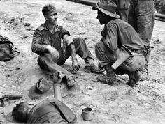 """6 May 1945. Australian Army Pvt. C.E. Collins (center) of """"C"""" Company, 2/48th Australian Infantry Battalion, who was wounded in the arm by a grenade during an attack on Sykes Feature during the Battle of Tarakan (Operation Oboe One) Collins had killed two Japanese soldiers and wounded another from approximately six feet range during the attack. Tarakan island, Borneo, Dutch East Indies (now, Tarakan island, North Kalimantan, Borneo, Indonesia)."""