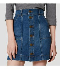 """In an authentic vintage mid wash, this button down denim style is equal parts pretty and polished. Button front. Belt loops. Front and back patch pockets. 17"""" long."""