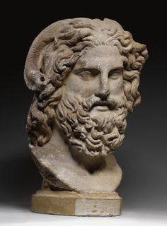 A Marble Head of Zeus Ammon, Roman Imperial (ca. AD 120-160) carved for insertion into a cult statue or bust of the Greco-Egyptian god, and inspired by an early Hellenistic sculpture derived from a Pheidian prototype, with majestic countenance, the great curling ram horns of Ammon emerging above his brow, with long beard and moustache, his deeply-drilled hair bound in a diadem and flowing in long leonine locks down to his shoulders. Height from base 19 in. 48.2 cm.