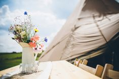 Simple flower arrangement of wild flowers in a porcelain jug at a Sami Tipi Wedding