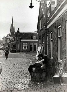 Wijk C   Jaren 30   De was schrobben (en drogen) voor je huis. Op de achtergrond de spits van de Monicakerk