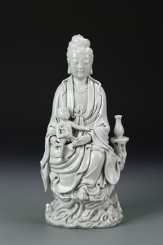 China, 19th C. blanc de chine Guanyin, in a seated position with a baby on her lap, the baby holding an auspicious symbol, glazed in a white hue with intricately carved drapery, on a raised base, and with minor damage on figure. Height 13 1/2 in.
