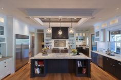 Ornate, modern kitchen features imposing island in black wood and light marble countertop, featuring dining area between shelving, and full sink.