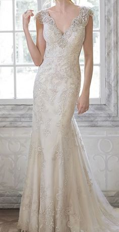 Delicate lace wedding dress with beaded cap sleeves.