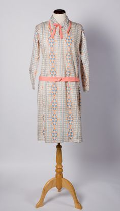 Dress ca 1926  A day dress of printed cotton patterned with vertical lines of wavy-paned diamonds against wavy vertical and horizontal lines in flesh pink and pale blue on white.