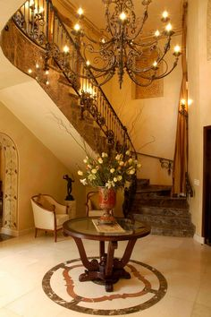 A contemporary home in Johannesburg, inspired by Classical Italian interior design and decoration. Sumptuous use of rich fabrics. Impressive chandelier in imposing entrance foyer.