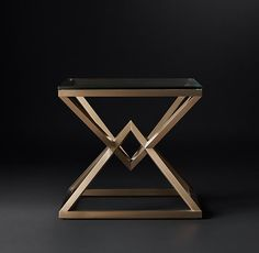 RH Modern's Empire Side Table:A dynamic double pyramid is the striking centerpiece of our 1970s-inspired table. An interpretation of a classic X-brace design, its tubular metal base supports a clear glass top that shows off its distinctive geometric form.