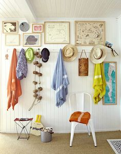 Wonderful wall of beach towels, hats, bags, etc with art above and chair below. LOVE