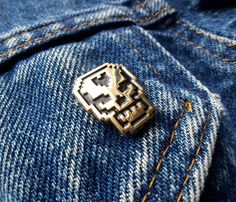 """8-Bit Skull Pin.BIT SKULL PIN. Game over man, game over.   0.75"""" x 0.6""""  Die struck soft-enamel pin with military clutch back"""