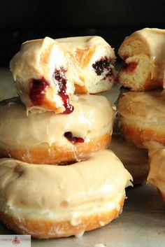 these are PEANUT BUTTER & JELLY DOUGHNUTS, my friend. fluffy glazed doughnuts filled with raspberry jam and covered with an additional peanut butter glaze.