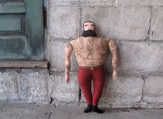 A beefy tattooed man doll, straight from the sideshow tent at the circus.