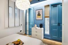 Dormitorio con pared azul y acceso a cuarto de baño
