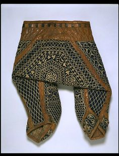 Breeches  Place of origin: Iran  Date:1800-1850  Materials and Techniques: cotton yarn, weaving, embroidering, printing, sewing, leather.  Museum number:841-1876  a pair of knee-length breeches, plain weave cotton embroidered with cotton in tambour or chain stitch, backed with resist dyed and printed plain weave cotton and padded, possibly with felt, with leather and with a belt and metal buckle.
