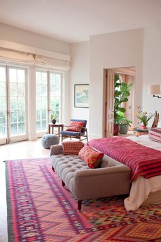 White bedspread, bold accent throw and rug and I LOVE the bench at the end of this bed