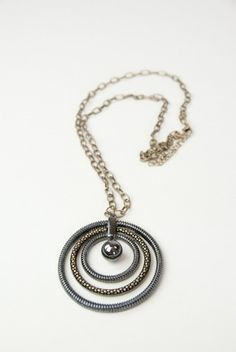 Spiral into your own fashion wonderland with this unique pendant necklace. Features multiple spirals of metal as well as a statement center. Lightweight.  $18.25