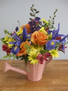 Showcasing the season of spring is this assortment of bright cheerful flowers in a unique watering can. Dark blue Iris, larkspur, orange roses, daisies, and alstroemeria combine to make this a memorable arrangement. $45.00