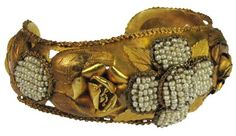 Persian bracelet:    22 karat gold solid cuff bracelet with raised flowers containing pearl beads. Probably belonged to a Queen.   500 BC
