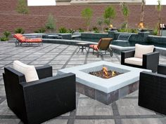 This massive paver patio is home to a custom stone fire pit and a long tiled water feature. Black wicker chairs with white patio cushions invite guests to conversational seating groups while orange cushioned lounge chairs add color to the space and provide separate areas for relaxation.