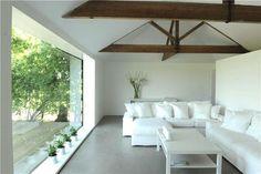 Oversize picture windows overlook an expansive deck area.