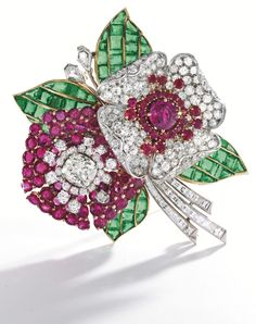 Ruby, Diamond and Emerald Flower Brooch, Circa 1930 Designed as a pair of blossoms framed by four leaves, the first centered by a cushion-cut diamond, framed by old European-cut diamonds, the petals set with round rubies, the other flowerhead reversely decorated, centered by a cushion-cut ruby framed by round rubies and old European-cut diamonds, the leaves set with calibré-cut emeralds, the stems set with square-cut diamonds, accented at the top by a pair of kite-shaped diamonds.