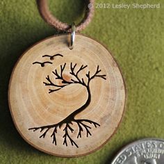 Arbutus branch section made into a pendant for a necklace featuring a pierced tree and birds.
