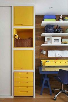 No canto de estudo da criança, nicho de laca amarela, mesa azul e painel de madeira de demolição. Vem ver mais inspirações no blog!