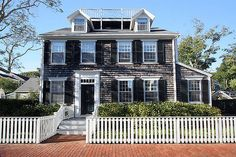 Nantucket house, cedar shakes, white trim, black shutters, white picket fence (note widow's walk) Photo by Heather Parker Photography