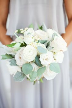 Gardening Roses classic all white bridesmaids bouquet of white garden roses, white ranunculus, white spray roses, button chamomile, eucalyptus and dusty miller is beautifully matched with the maids gown of pale grey. Bridesmaid Bouquet White, White Rose Bouquet, White Ranunculus, White Wedding Bouquets, Flower Bouquet Wedding, Floral Wedding, Prom Bouquet, Purple Bouquets, Flower Bouquets