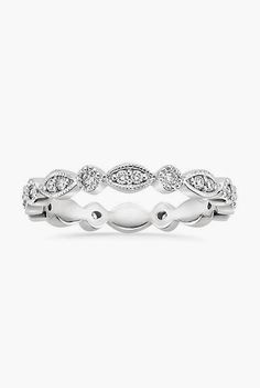 Harmonious diamond-accented round and marquise shapes encircle the finger for a delicate wedding band