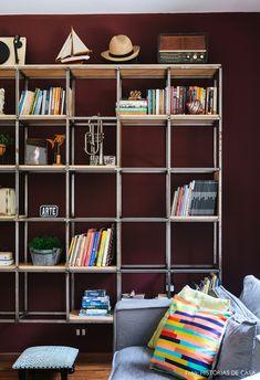 Estante metálica com prateleira de madeira, sofá com almofadas coloridas e parede pintada em tom de beringela.