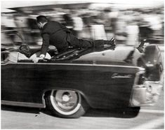 The President has been shot! 11-22-63  Jackie leans over him while a Secret Service agent attempts to get to him over the rear of the convertible.