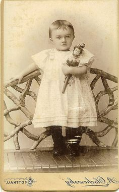 Beautiful child holding some sort of vintage puppet doll.