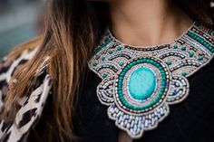 This beautiful bib necklace by @theshoppingbag  features intricately placed beads in hues of white, turquoise and gray. Perfected with a felt back, black ribbon tie, and large turquoise stone center, this exquisite necklace will sure to make a colorful statement!