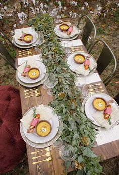 Fall-Inspired Wedding Table: Brown Wooden Table with Green Leaf Table Runner and White and Gold China | Brides.com