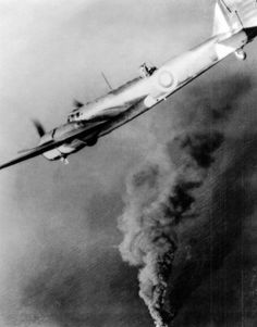 British Bristol Blenheim flying over a burning German tanker in the North Sea.