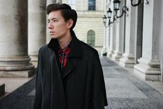 Fashion and Art in Munich. Red and black check shirt and black cape